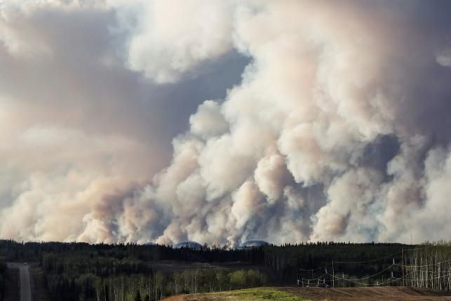 Canadian wildfire edges south, leaves thousands stranded